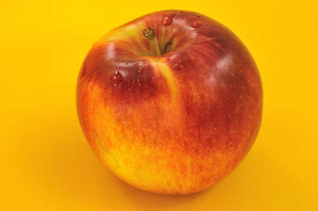 red appetizing apple with drops of water on a yellow background Stock Photo