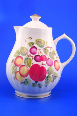 Painted white pitcher photographed in front of blue background  Stock Photo