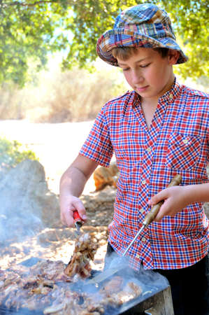 teenager in a park on a holiday to cook meat and steaks on the grill photo