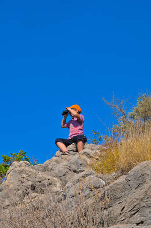 boy sitting on a rock on top of a mountain and sees the neighborhood through binoculars photo
