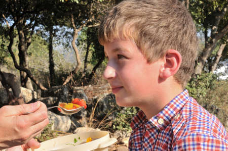 boy looks at his mother who gave him a spoonful of salad, so he tried it photo