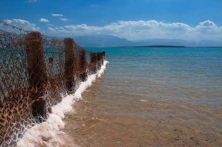 A fence separates the beach hotels covered Dead Sea salts