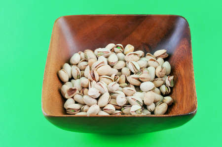 Pistachios roasted with salt lie in a wooden platter against a green background