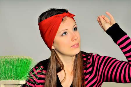 部屋の掃除を準備する彼の頭に赤いハンカチを持つ少女 写真素材