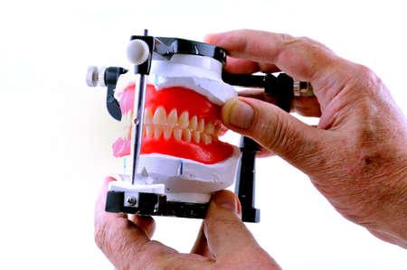 Le technicien détient les prothèses dentaires qui sont attachés à une machine spéciale Banque d'images - 9861959