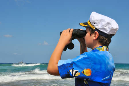 The Boy in the naval cap, considering the ship with binoculars who sailed to sea Stock Photo - 10467689