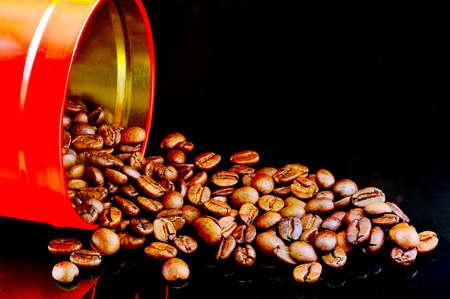 黒の背景に銀行の反射で赤の画像から注がれる熱いコーヒー粒 写真素材