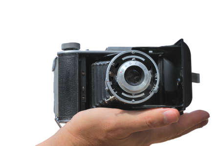 Old camera lies in the palm of the photographer isolated against a white background