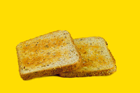 Two slices of white bread flour coarse baked in a toaster lie against a yellow background photo
