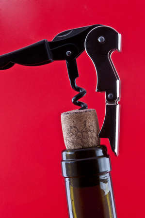 Dark brown bottle with a cork and corkscrew which is screwed into the cork photo