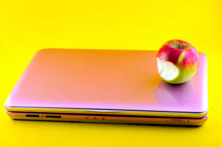 Pink computer that is bitten apple, photographed against a yellow background photo