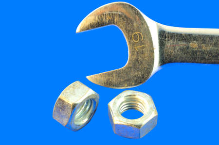 chromeplated: Chrome-plated wrench and two chrome-plated nuts, against a blue background