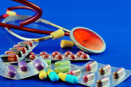 Multi-colored tablets laid out on the table next to stethoscope 