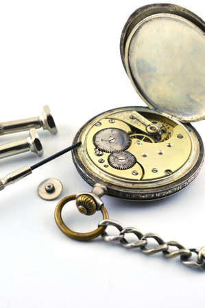 The old silver watch and a screwdriver to repair on the table, against a white background