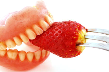 artificial teeth: Strawberries sandwiched  artificial teeth, photographed against a white background