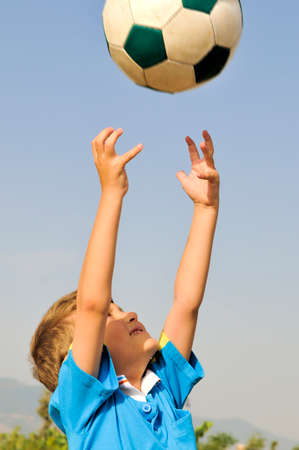 threw: Little football player catches a ball arms, which is highly threw his father Stock Photo