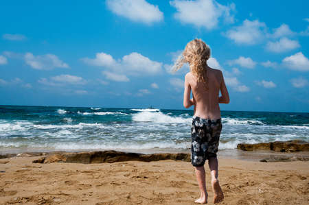 sees: The boy saw the sea warship and sees it standing on the beach Stock Photo