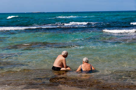 cool off: A pair of elderly pensioners came on a hot day to sit and cool off in the sea water Stock Photo