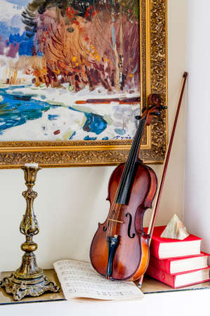 cornerstone: Violin and old candlestick stand on the table under the painting, along with books and a cairn, the cornerstone