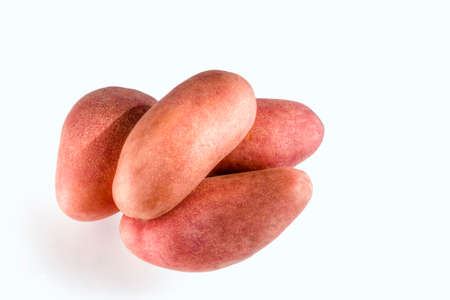 heaped: Four large red potatoes are heaped against a white background