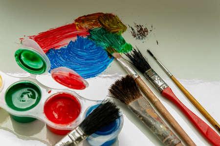 Pinceaux et peinture sur l'artiste blanc fait quelques coups et brosse gauche couché