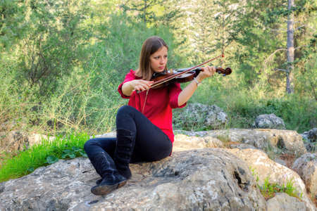 arts culture and entertainment: Girl playing the violin in the woods hoping to attract wild birds