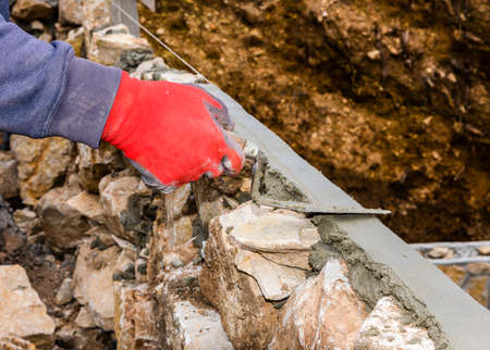 Work bricklayer smoothies strip of concrete on a stone fence