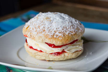 Bun of tender puff pastry with white custard and strawberry jam