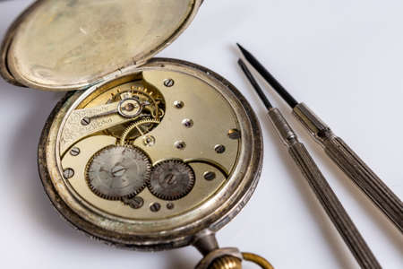Antiques, vintage swiss pocket watch, two screwdrivers and tweezers lie on a white plastic table 免版税图像