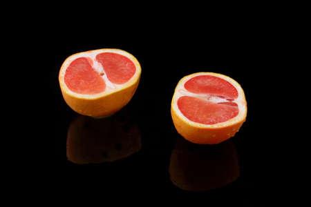 specular: a halved grapefruit on black background