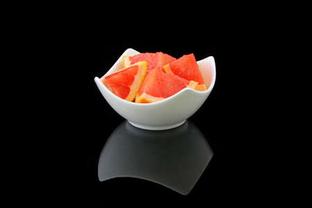 specular: grapefruit pieces in a porcelain bowl Stock Photo