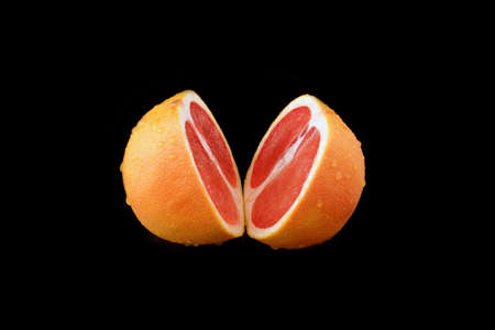 grapefruit: a divided grapefruit on black background