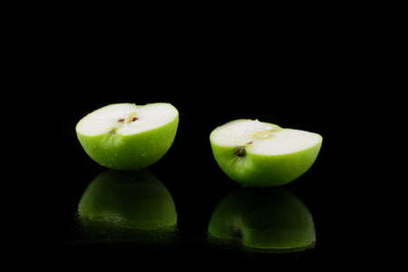 halved  half: a green sliced apple on black Stock Photo