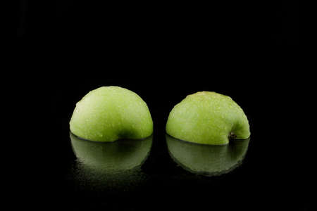 halved: a green sliced apple on black Stock Photo