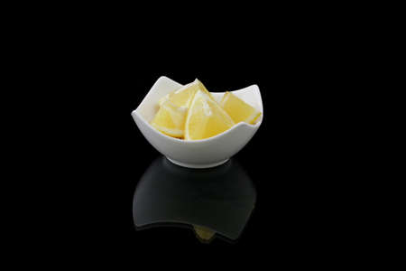 morsels: lemons morsels in a dish on black