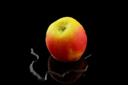 yellow red: a yellow red apple on black background Stock Photo