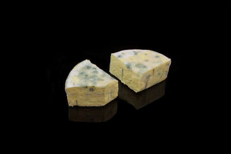 nutty: Two pieces blue cheese on black background