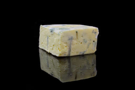 nutty: a piece of blue cheese on black background Stock Photo