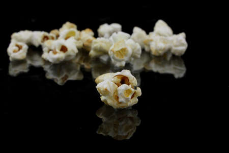 puffed: popcorn with reflection on black background