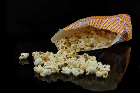 puffed: a bag with popcorn on black background Stock Photo