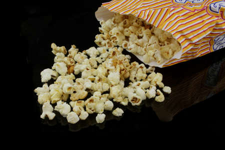 distributed: popcorn bag dumped on black background