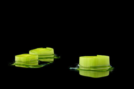 wide  wet: three leek pieces with water on black background