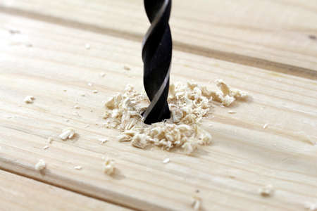 triplet: a wood drill pierced into a wooden board Stock Photo