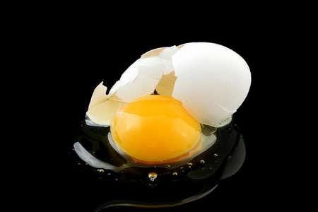 broken egg: a broken egg on black background