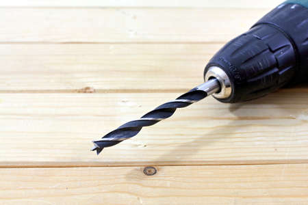 triplet: close up of a drill on wood