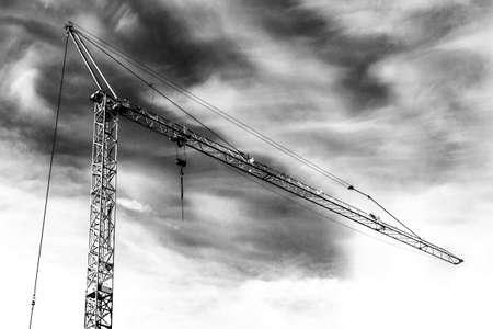 a construction crane outdoors under cloudy sky Stock Photo