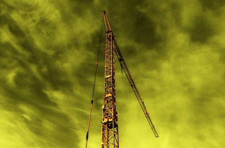 a construction crane outdoors under cloudy sky on yellow