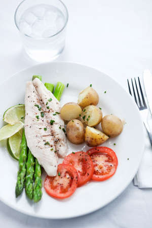 knife tomato: Fish dish with potatoes, asparagus, tomatoes, limes on the plate Stock Photo