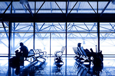 Silhouettes of people traveling on airport; waiting at the plane boarding gates. 新闻类图片