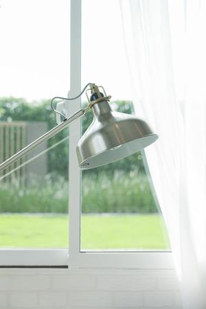 floor lamp: Metal floor lamp standing by the window Stock Photo